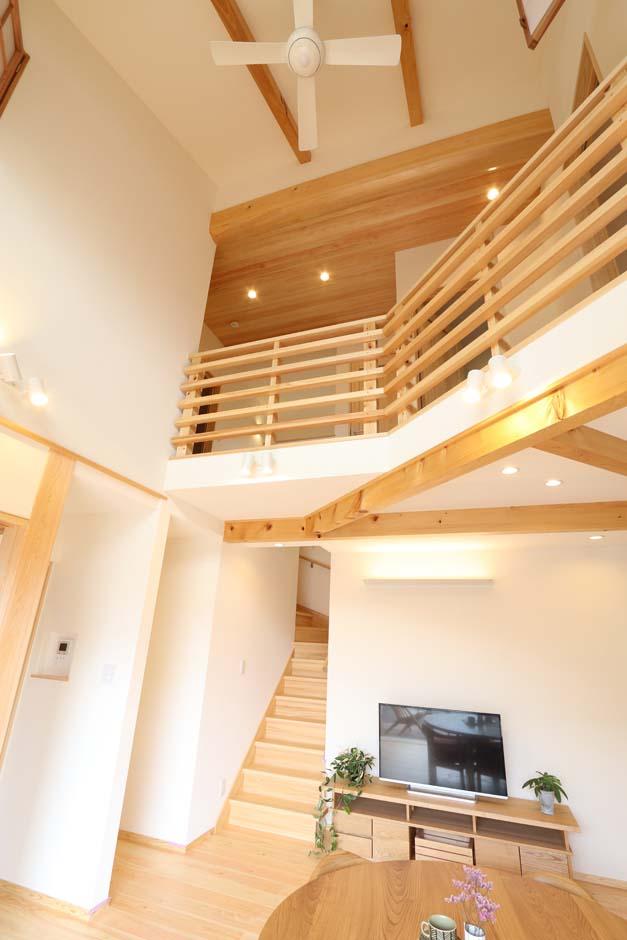 リビング階段と吹き抜けが、1階の住空間と2階の居室とを繋ぐ。見上ゲルト目に入る太鼓梁の丸みが柔らかな雰囲気を醸し出す