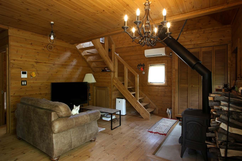 BESS浜松【自然素材、ペット、インテリア】薪ストーブは玄関土間を拡張して設置。木の床と比べて汚れや火の粉を気にする必要がなく、思う存分使うことができる。また、標準仕様のストレート階段をL字型に変更することで生まれた空間を収納庫として活用