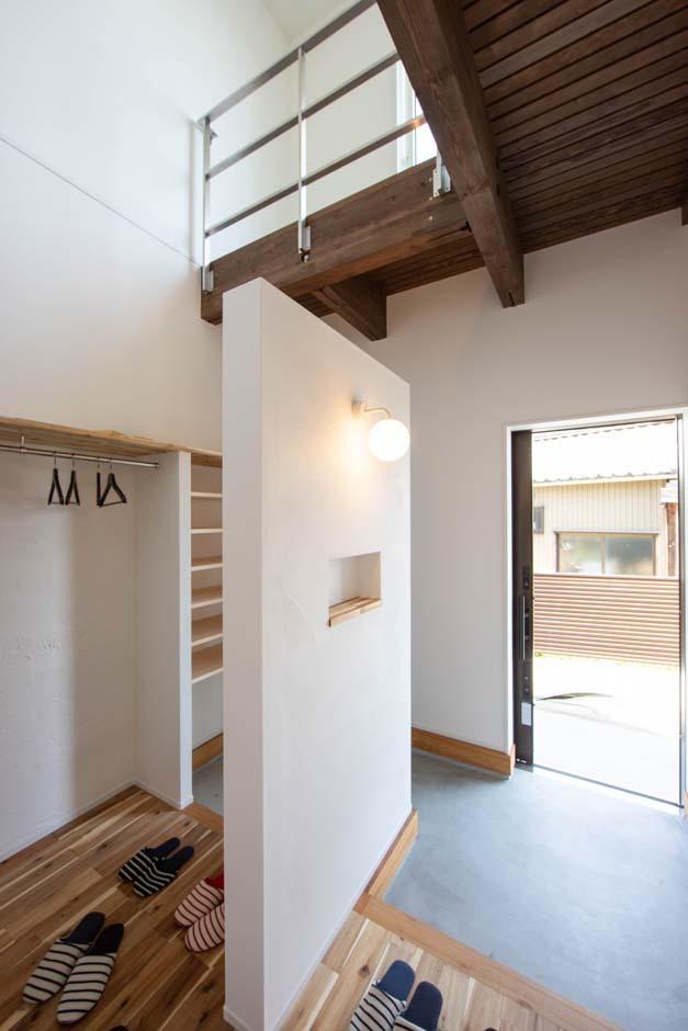 KOZEN-STYLE コバヤシホーム【デザイン住宅、自然素材、省エネ】ゲスト用と家族用に仕切った玄関はシューズクロークと外着をかけるハンガー付き。吹抜けの上部の窓から明るさを確保し、開放感と清潔感溢れる印象に。2階の窓の先にはベランダがある