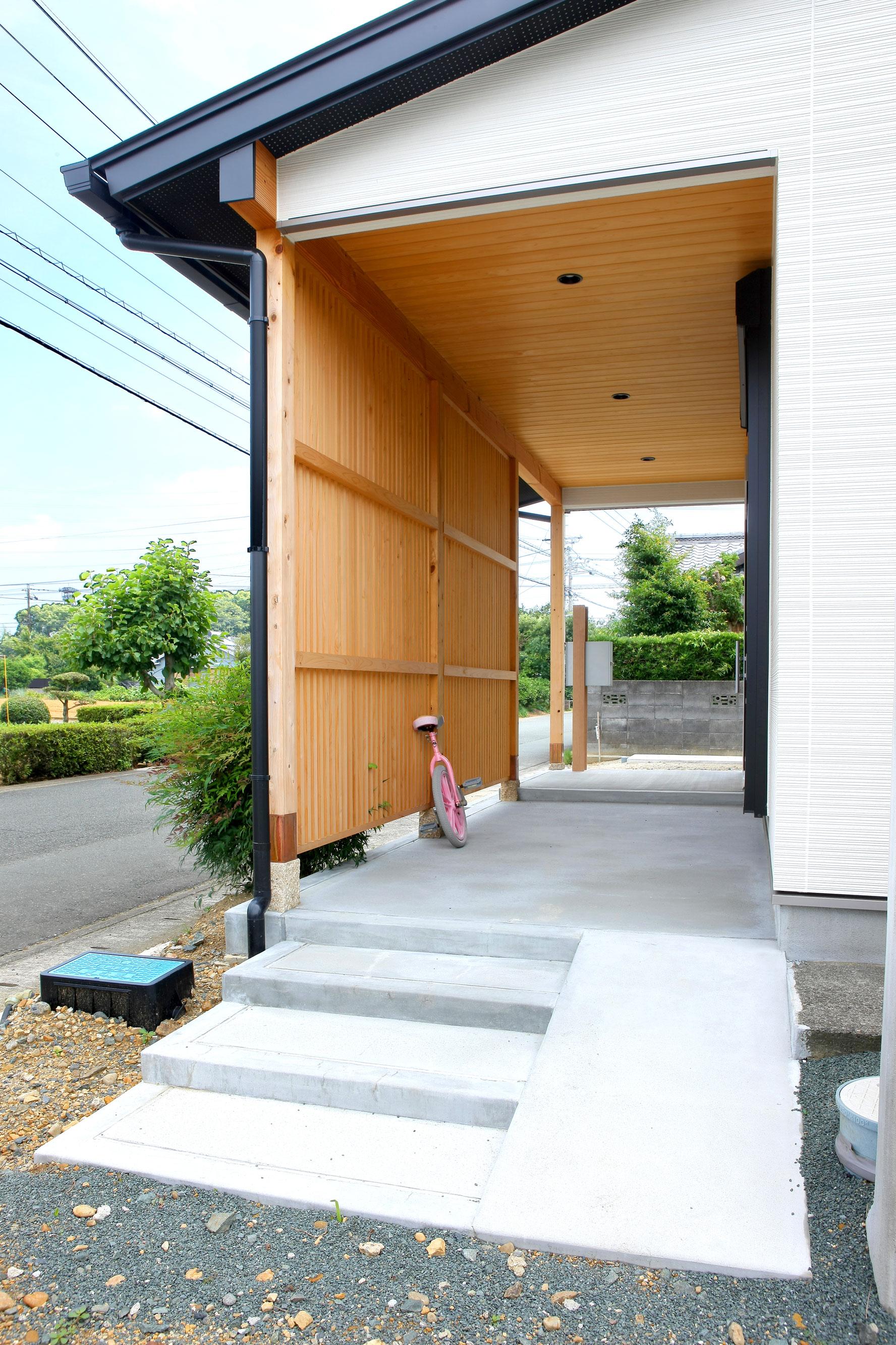 玄関ポーチは、深く張り出した庇で十分な広さを確保し、雨の日の出入りも快適に。スリット格子で通りからの視線を遮り、採光・通風を確保している。ブロック塀を撤去したことにより、道路に出ることなく直接駐車場に出入りできるようになった