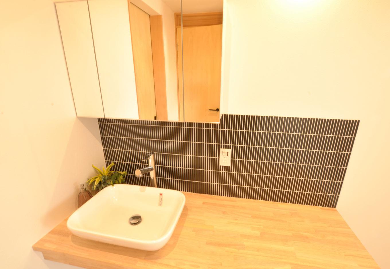 Asobi-創家(アソビスミカ)/ナカジツ【デザイン住宅、趣味、建築家】洗面にタイルをあしらって上品な印象に。幅広の洗面台で洗濯物をたたんだり、アイロンをかけたり、家事がはかどる