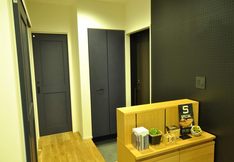 Asobi-創家(アソビスミカ)/ナカジツ【デザイン住宅、趣味、建築家】玄関ホールはあえて壁をなくすことで、空間にゆとりが生まれ、視覚的な広さを感じられる。黒いボードは音楽室などで見る吸音材を意匠的に使用