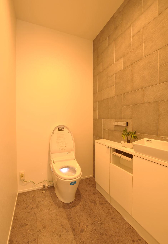 Asobi-創家(アソビスミカ)/ナカジツ【デザイン住宅、省エネ、建築家】トイレの壁にグレーのタイルをあしらったスタイリッシュな空間。幅広の空間にすることで、ゆったりとした雰囲気に