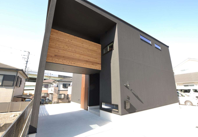 Asobi-創家(アソビスミカ)/ナカジツ【デザイン住宅、省エネ、建築家】黒色の塗り壁がモダンな外観に木製のインナーテラスが映える。玄関前をインナーガレージにすることで雨の日でもぬれずに家の中に入ることができる