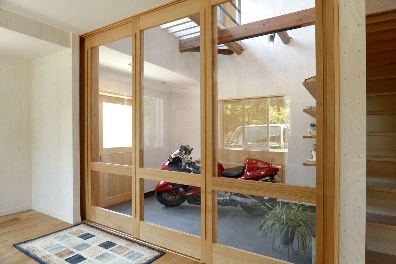 エコフィールド|リビングとガレージは仕切り扉はガラスに。ご主人のバイクもインテリアの一部
