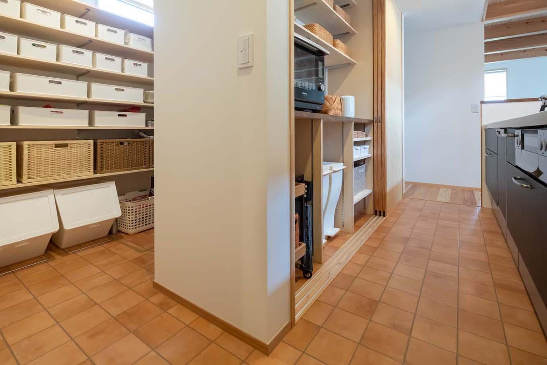 あだちの家。足立建築【子育て、収納力、間取り】奥さまの家事ラク・育児ラク動線に配慮して造作したバックヤードは、引き戸で調理家電をさっと隠せる食器棚と、その裏にある大容量パントリーの2本立て。収納ボックスのデザインや素材にもこだわり、「見せる収納」を実現している