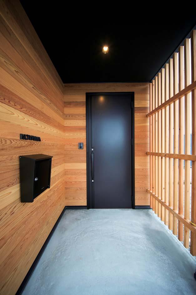 ARRCH アーチ【デザイン住宅、建築家、インテリア】板張りの外壁と格子戸に囲まれた玄関ポーチ。玄関ドアやポスト、天井は黒で統一
