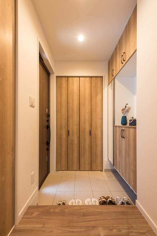 明和住宅【子育て、収納力、間取り】たっぷりの収納を用意した玄関ホール。建具も木調のものを選んで、フローリングの色と統一。スッキリとした空間に