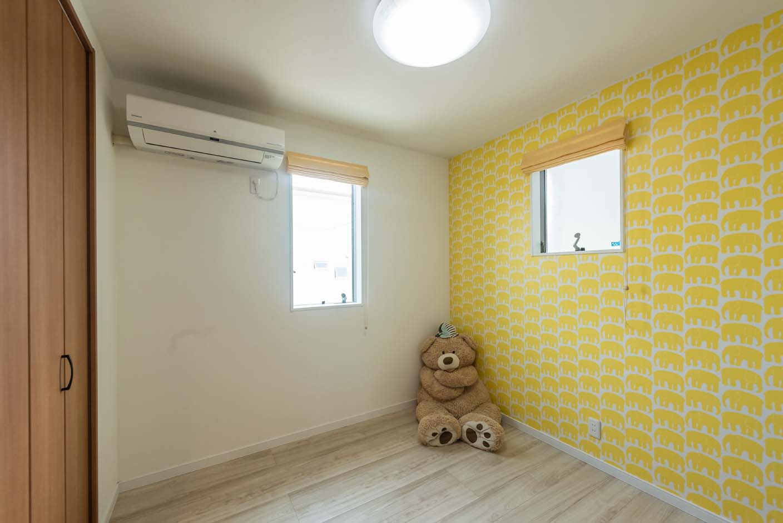 明和住宅【子育て、収納力、間取り】3人姉妹なので、子ども部屋の一つは個室で用意。黄色い象のモチーフが個性的なアクセントクロス。子どもが成長して使うまではご主人の部屋として使用している
