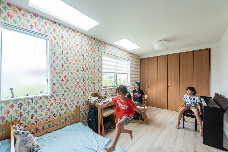 明和住宅【子育て、収納力、間取り】カラフルな北欧モチーフのクロスを用いた子ども部屋。家づくりの一番の希望は、3人の娘さんの個室をつくること。将来はセンターで分割も可能。北側天井のトップライトで明かりを取り込む