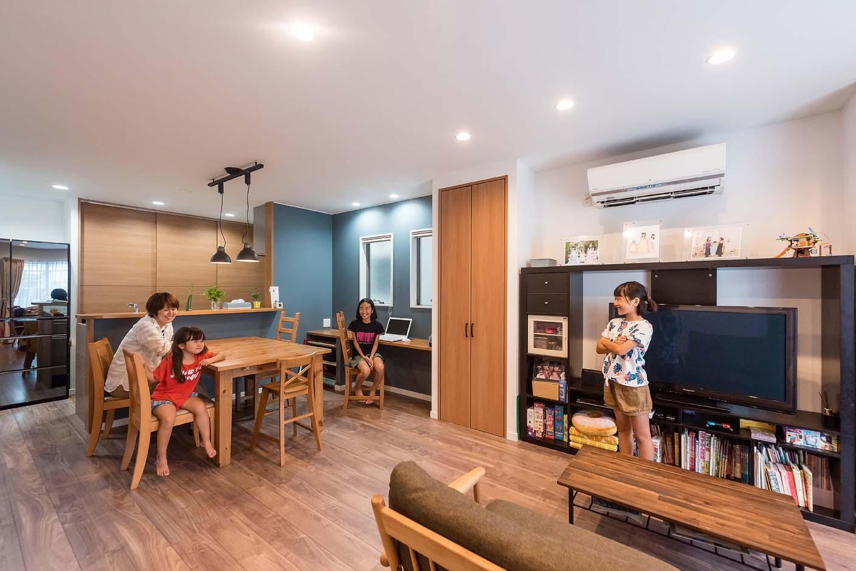明和住宅【子育て、収納力、間取り】5人家族が集まるリビングは、広さもこだわり。テレビボードを挟んで用意した2つの収納でスッキリとした空間を保つ。カウンターデスクは、子どもの宿題や奥さまのちょっとした作業時に便利に使える