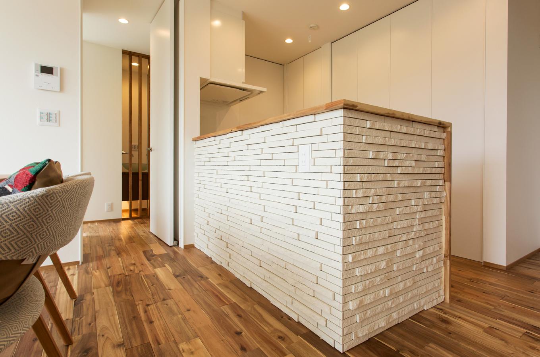 ARRCH アーチ【デザイン住宅、子育て、間取り】キッチンに立つとLDK全体を見渡せる。造作のカップボードは収納力も見映えもバッチリ。キッチンの腰壁がLDKのアクセントになっている。ワークトップの手元を隠すため、腰壁は高めに設定
