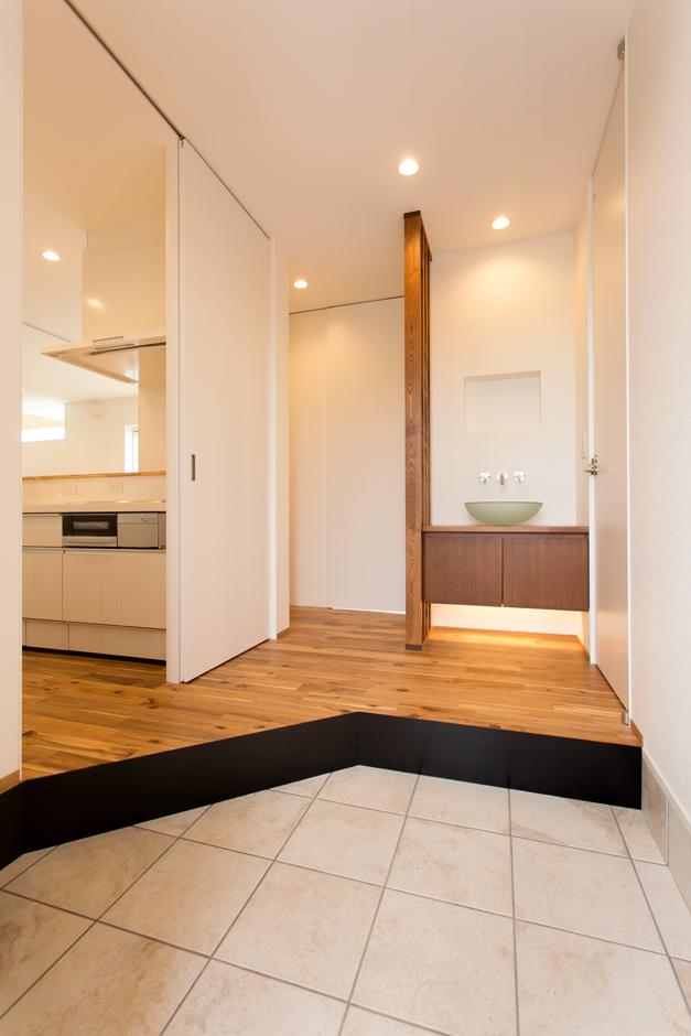 ARRCH アーチ【デザイン住宅、子育て、間取り】北玄関は暗くなりがちなので、スペースを広々と確保。玄関のすぐ正面には手洗い場を設け、子どもが帰って来た時にすぐに手洗い・うがいができるようにした。食品類をまとめ買いすることが多い奥さまのために、キッチンへのアクセスも短縮。キッチン裏のカップボードは玄関からも出し入れ可能