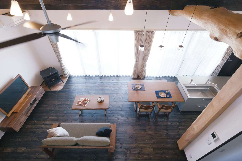 住まいるコーポレーション【デザイン住宅、自然素材、平屋】ロフトから眺めたリビング。自然塗料で濃く着色した床がアンティーク感に溢れた空間を演出