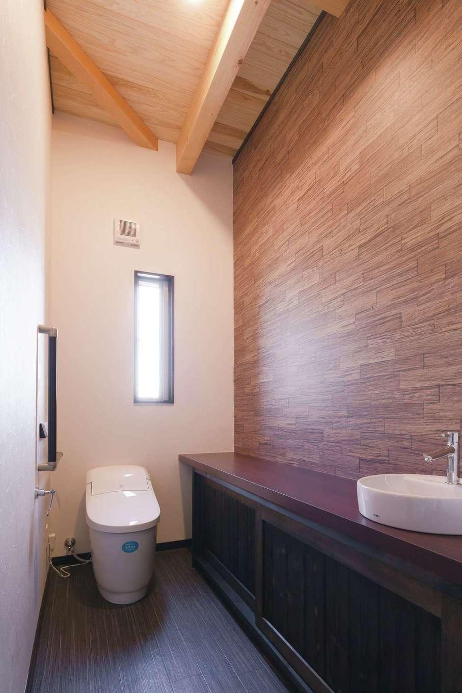 住まいるコーポレーション【デザイン住宅、自然素材、平屋】トイレも落ち着いたトーンでシックにコーディネート。濃い茶系のカウンターが空間を引き締め、アジアン調の落ち着いた雰囲気を醸し出す。勾配天井の板張りもそのまま活かしている