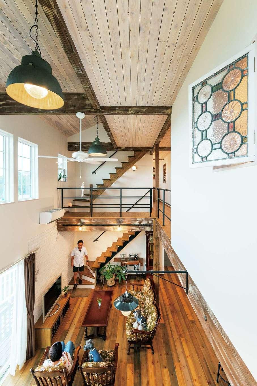 富士ホームズデザイン【デザイン住宅、輸入住宅、インテリア】2階キャットウォークから吹き抜けを見通す。天井の板は木目が見える程度に塗り、開放感にあたたかみをブレンド。照明はベルギーの工場で使われていたもので、ステンドグラスは100年以上の時を越えたアンティーク。唯一無二の雰囲気づくりに大きく貢献している