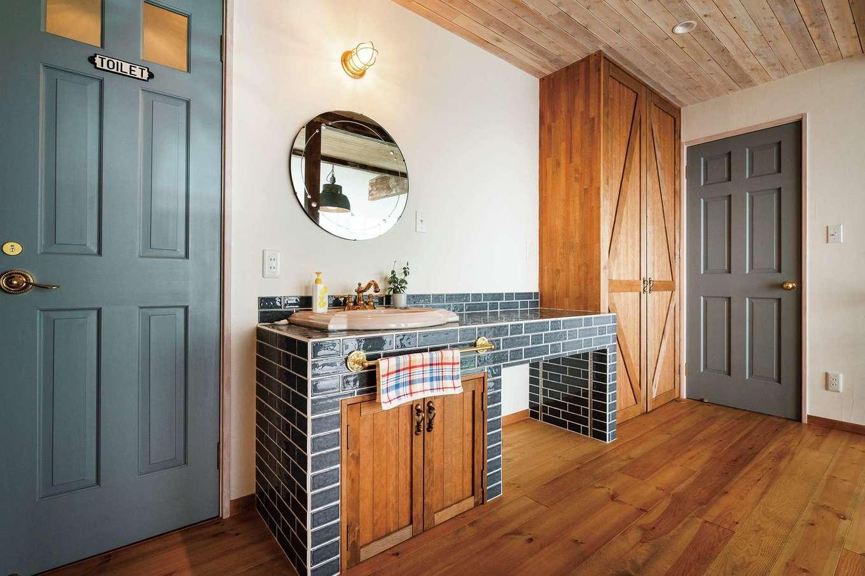 富士ホームズデザイン【デザイン住宅、輸入住宅、インテリア】タイル仕立ての2階洗面台。広く取られたカウンターはアイロン掛けや洗濯物をたたむのに重宝。建具のトーンもそろえられている