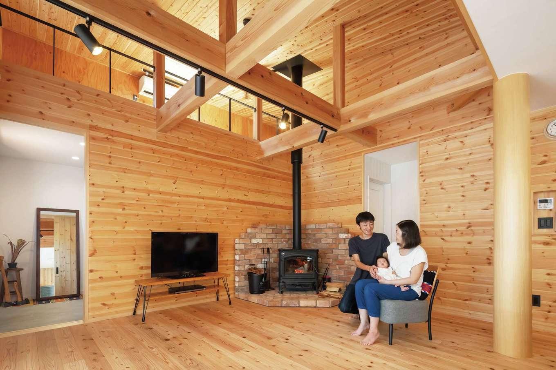 フジモクの家(富士木材)【デザイン住宅、自然素材、平屋】無垢材を惜しみなく使った室内は、アウトドア好きな夫婦にぴったりの山小屋をイメージ。8寸の大黒柱はヒノキのみがき丸太、床は天竜杉、梁はオクシズ(奥静岡)材、壁はパイン材。大屋根を採用したことで吹抜けと小屋裏が生まれ、平屋とは思えないほどの開放感がある