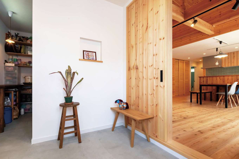 フジモクの家(富士木材)【デザイン住宅、自然素材、平屋】シンプル&ナチュラルな土間玄関。天井まで届くハイドアは壁と同じパイン材で、空間に一体感が生まれた。奥はキャンドル作家でもある奥さまの アトリエ