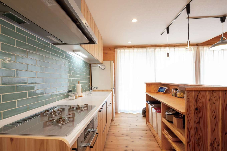 フジモクの家(富士木材)【デザイン住宅、自然素材、平屋】なるべく部屋を広く使えるようキッチンは壁付けに。アイランドの木製キャビネットは友人の手づくり。淡いブルーのタイルがアクセントに