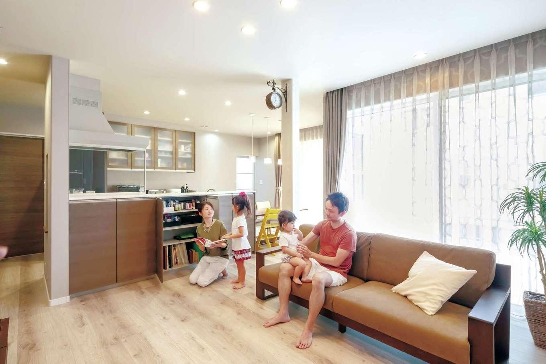 遠鉄ホーム【子育て、収納力、間取り】南面に大開口を設けた明るいLDK。フローリングの色と質感に合わせて、クロスは淡いグレーを採用。キッチンを中心にぐるぐると回遊できる間取りが共働き・子育てママの家事負担を軽減する