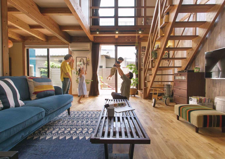 サイエンスホーム【デザイン住宅、自然素材、省エネ】開放感あふれる吹抜けのリビング。目線がタテ・ヨコに抜けるので、実面積よりも広く感じられる。無垢のダークウォールナットの床とアンティーク調の家具がマッチして、イメージ通りの心地いい空間に仕上がった
