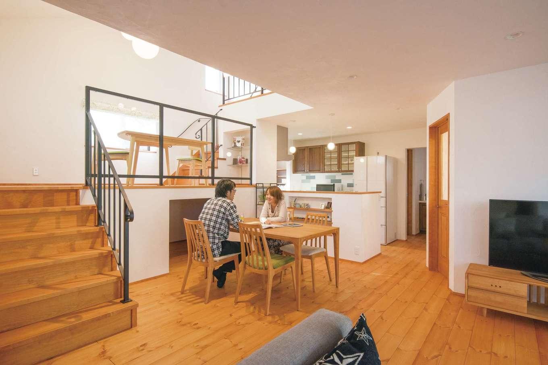 アイジースタイルハウス【デザイン住宅、自然素材、省エネ】スキップフロア&吹抜けのあるLDK。キッチンからも全体が見渡せて開放感抜群。無垢のパイン床と漆喰の塗り壁にアイアンの手すりが絶妙にマッチ。スキップフロアの下は4畳の蔵収納