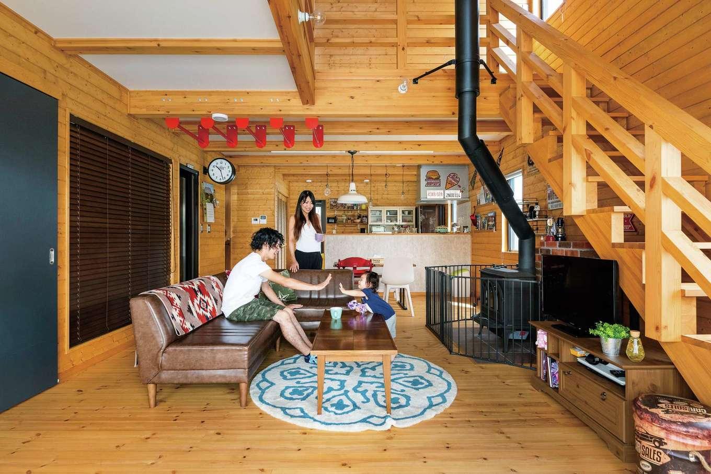 BESS浜松【子育て、趣味、インテリア】パイン無垢材を張った床や壁に囲まれ、吹き抜けのあるリビングは広々として居心地がいい。薪ストーブや天井の赤いウンテイなど、遊び心もいっぱいだ