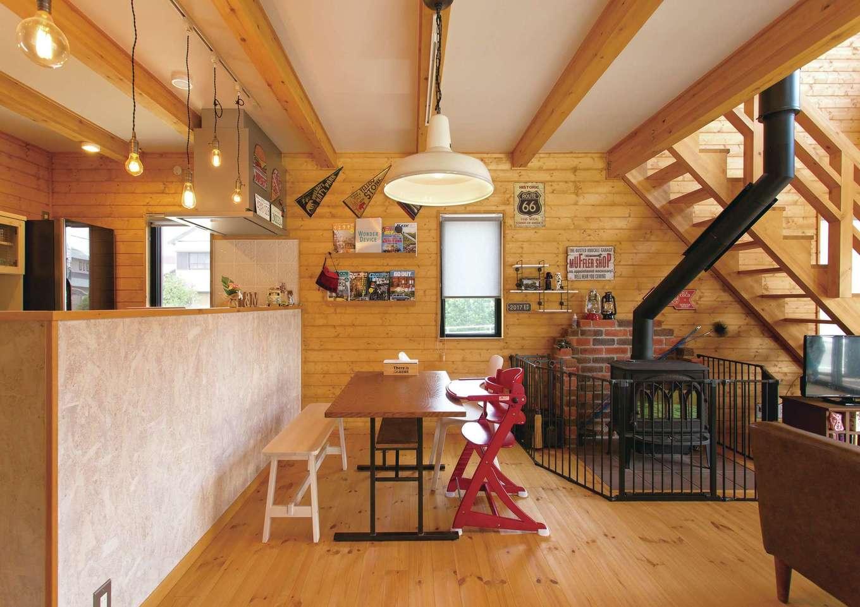 BESS浜松【子育て、趣味、インテリア】OSB合板で仕上げたキッチンは、白い塗料を塗ってカフェ風に演出。壁のマガジンラックはご主人の手作り。トラフィックサインやフラッグなど、バイクや車関連のアイテムも似合う