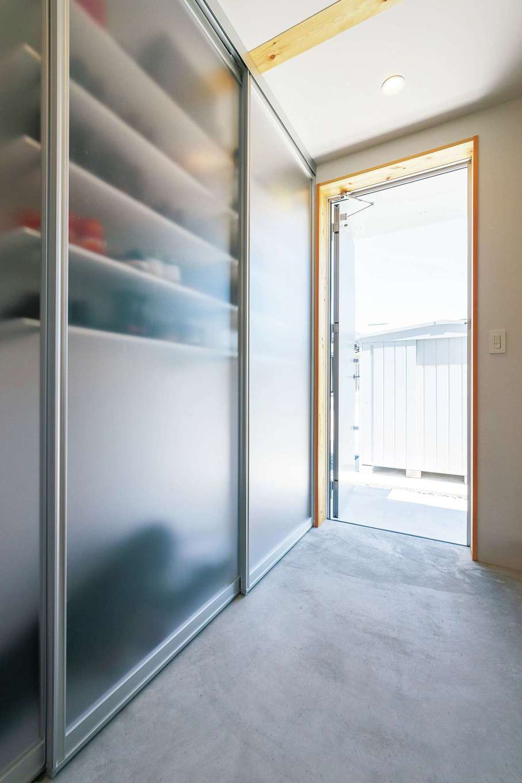 シンプルな土間玄関。左側の壁はすべて収納棚