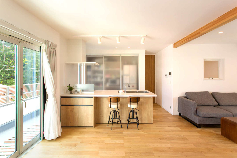 コバケンホーム(小林建設)【子育て、自然素材、間取り】天然木と漆喰を贅沢に使い、ナチュラルなテイストに仕上げた2階のLDK。オークの床に合わせてキッチンパネルやソファをコーディネートした。現しの梁にも心が癒される