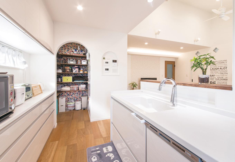 誠一建設 【子育て、二世帯住宅、間取り】リビングダイニングを見渡せるキッチン横には、たっぷり収納できるパントリーを用意。奥さまこだわりのRにした入り口やタイル風の壁紙がかわいい