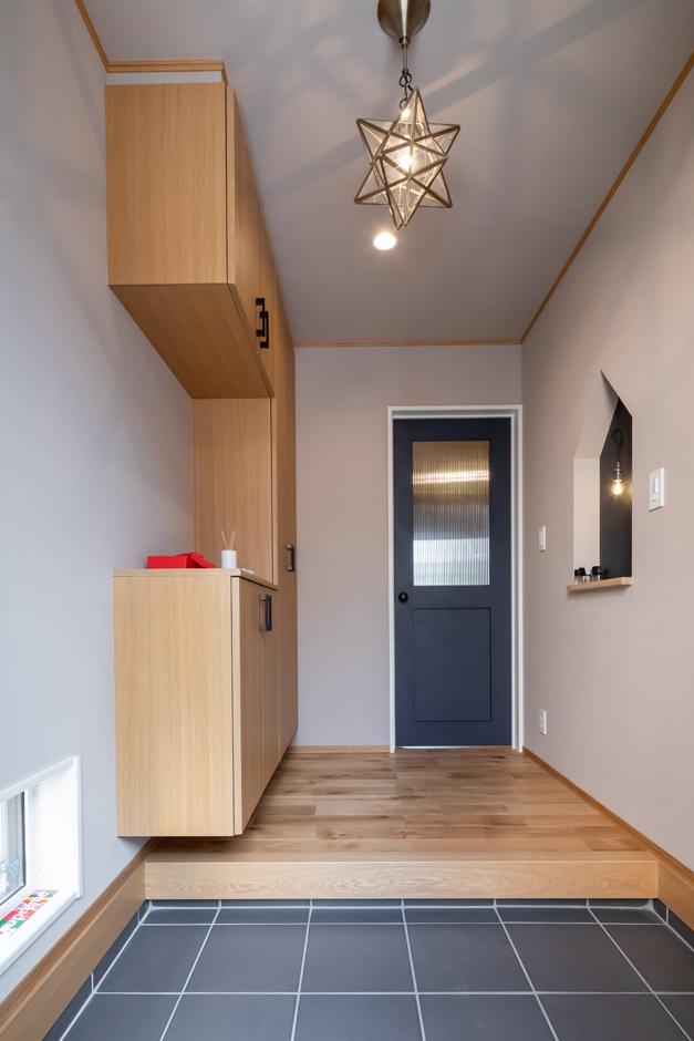 アイジーホーム 【デザイン住宅、間取り、インテリア】玄関ホールは照明のつくりだす表情と切妻型のニッチが印象的。リビングにつながるネイビーのドアは、やわらかさのある丸ノブと色味にこだわった