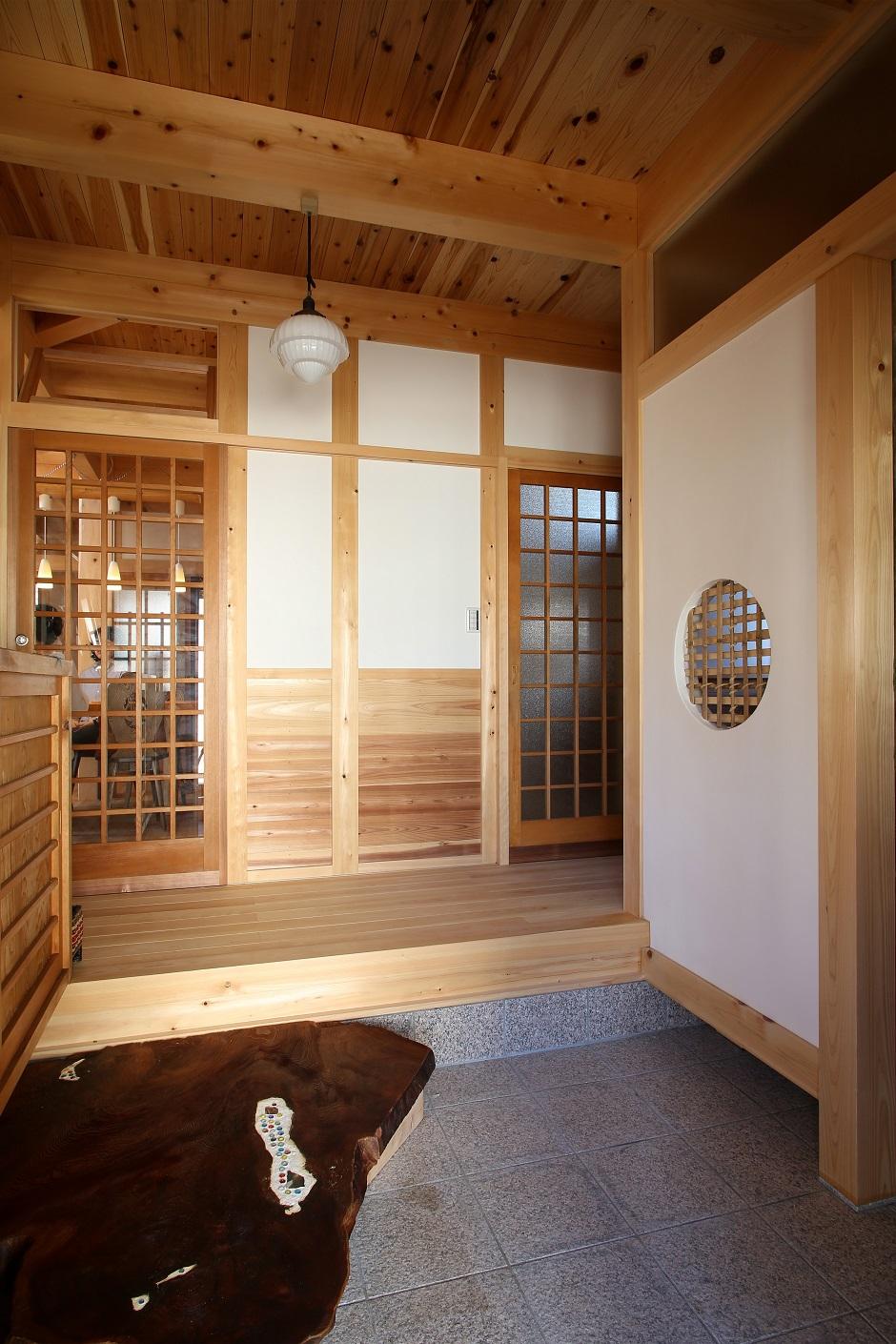 ほるくす【和風、自然素材、ペット】玄関の収納スペースには茶室を思わす下地窓を配し、柔らかな光を取り入れている。扉を開けば、ヒノキの香りがふわり。