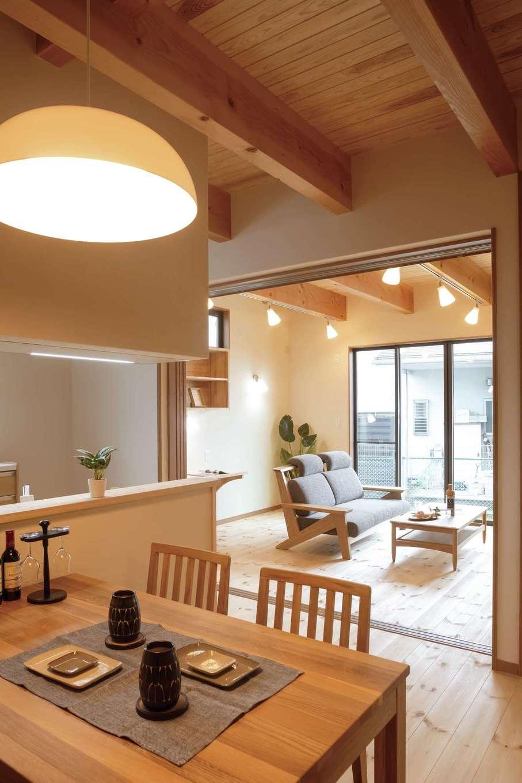 住まいるコーポレーション【二世帯住宅、自然素材、間取り】対面キッチンの正面にダイニングテーブルを配置。来客時を考慮して、ダイニングキッチンとリビングの間には仕切り戸を設置。冷暖房の節約にも役立っている