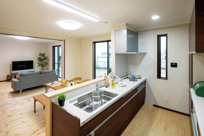 住まいるコーポレーション【二世帯住宅、自然素材、間取り】ワークスペースにゆとりを持たせた対面キッチン。キッチンの正面にダイニングとリビングが広がる。ダイニングとリビングの間を引き戸で仕切ることもできる