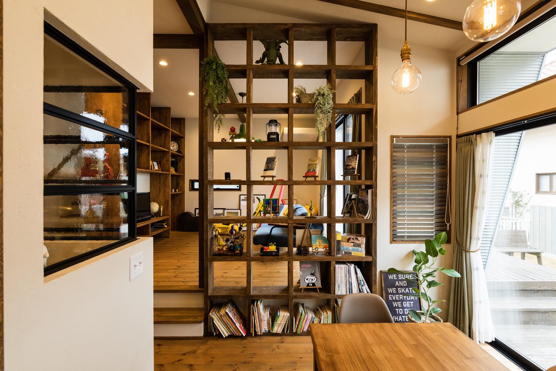 Select工房【デザイン住宅、趣味、ガレージ】ダイニングからリビングを望むと、エイジング加工した造作棚を通して視線が繋がる仕組み。ゆるやかに仕切られた心地よさと、空間の広がりに心が落ち着く。パイン無垢材の床は21mmと厚く、寒い日でも素足で過ごせるほど肌馴染みがいい