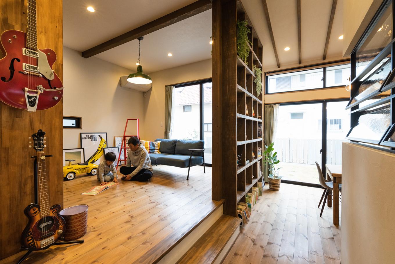 Select工房【デザイン住宅、趣味、ガレージ】玄関ホールを直進すると、緩やかに区切られたLDKが目の前に広がる。右手の開閉式窓の奥にはキッチン、その隣にはダイニング、さらに書棚を挟んで左手にリビング。スキップフロアの高低差、大きな窓がタテの広がりを生み、畳数以上に開放感を感じる