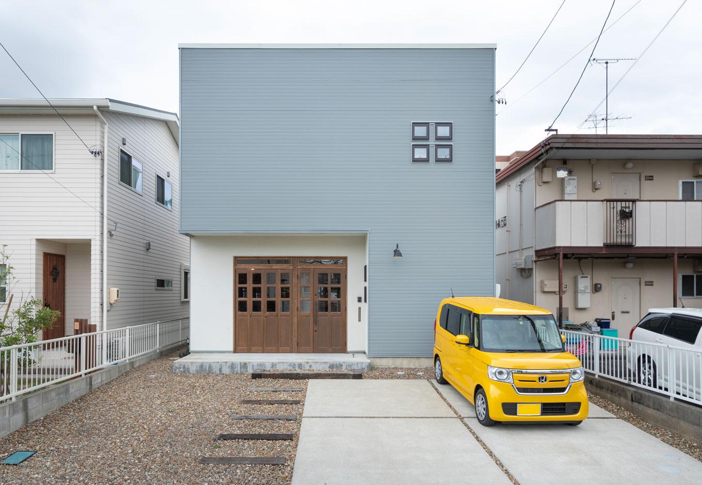 Select工房【デザイン住宅、趣味、ガレージ】ガルバリウム鋼板と塗り壁を組み合わせた外観はごくシンプル。オリジナルの木製ドアは、右側が玄関、左側が蛇腹に開くガレージ用だ