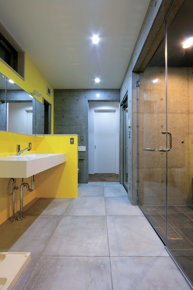 BAUM HOME(岩崎工務店)【デザイン住宅、平屋、鉄骨鉄筋コンクリート構造】キッチンからも寝室からもつながるサニタリー。鮮やかなイエローが差し色に。ガラス張りの浴室は造作で、中庭に面している