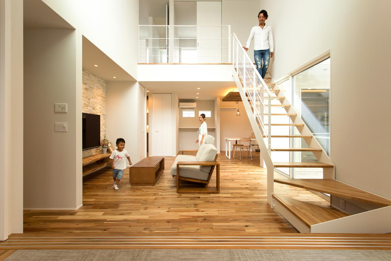 ARRCH アーチ【デザイン住宅、間取り、ガレージ】LDKはテラスデッキを囲むL字型。吹抜けと大きな窓が明るさと開放感をもたらす一方で、近隣の視線を遮り、プライベート感溢れる空間を実現。アイアンの白い手すりの階段がアクセントとなって広い空間を引き立てている