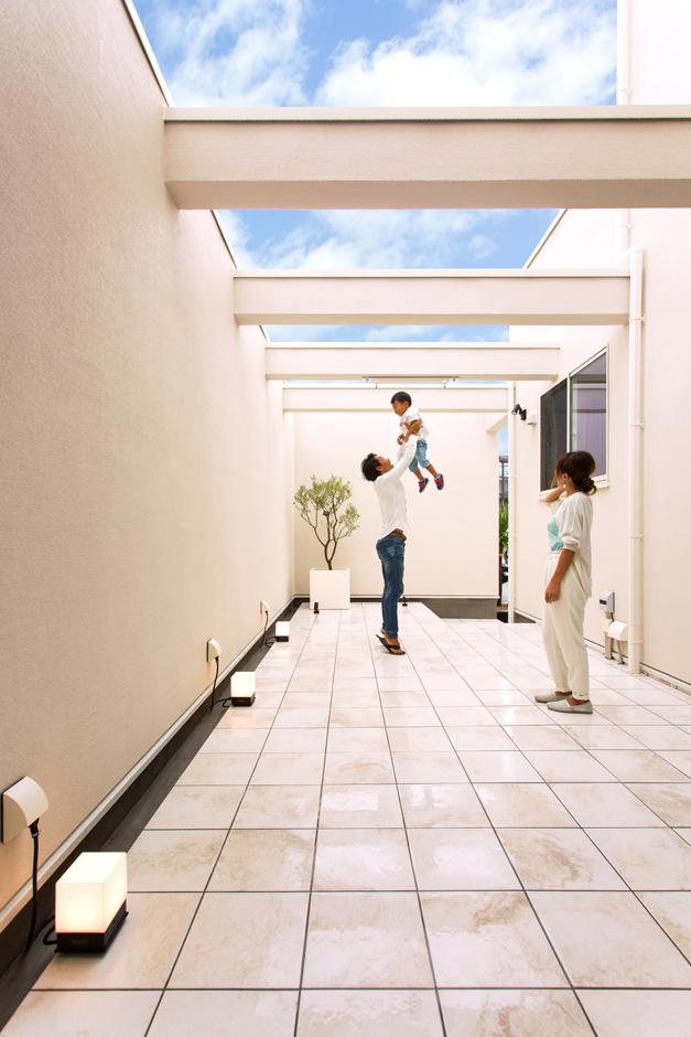ARRCH アーチ【デザイン住宅、間取り、ガレージ】タイル敷きのテラスデッキ。外壁と同素材の壁で中庭のように囲み、プライバシーを確保。壁がファサードのデザイン上でも効果的な役目を果たしている。梁の影が広い空間に変化をもたらし、非日常感溢れるリゾートチックな空間が実現