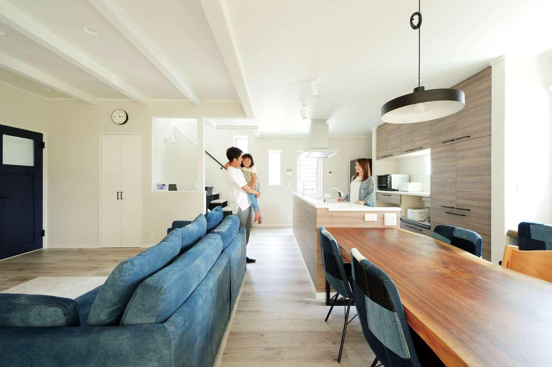 ほっと住まいる【デザイン住宅、自然素材、間取り】床、壁、天井を白で統一したシンプルなLDK。リビングとダイニングの天井の高さを変えてアクセントをつけた。ウォルナットのダイニングテーブルは『ほっと住まいる』からのプレゼント