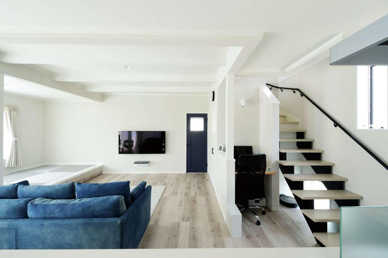 ほっと住まいる【デザイン住宅、自然素材、間取り】北欧スタイルにコーディネートしたリビング。階段下のデッドスペースを活かしてPCコーナーに。スケルトンの階段から視線が抜け、より開放的に感じられる