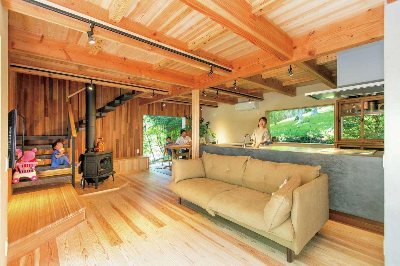 マクス (マクス一級建築士事務所)【デザイン住宅、自然素材、インテリア】リビングはどの方向も森に向かって開かれている。薪ストーブとシンプル造作キッチンが木の質感によく似合う