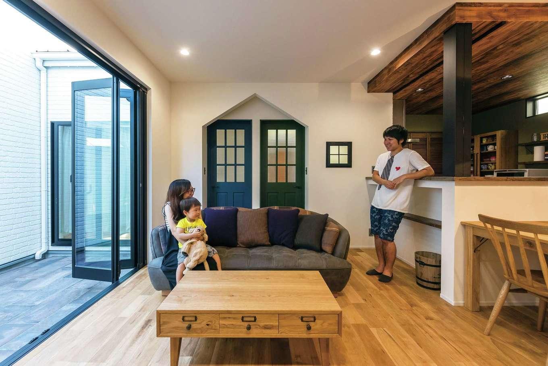 ブルックリンスタイルにコーディネートしたLDK。無垢の床と同じオーク材の家具、キッチンを購入して統一感を出した。黒いアイアンで巻いた柱がウッディな空間を引き締めている。三角形に抜いた壁も部屋のアクセントに。南面の全開口サッシを開けると中庭との一体感が生まれる
