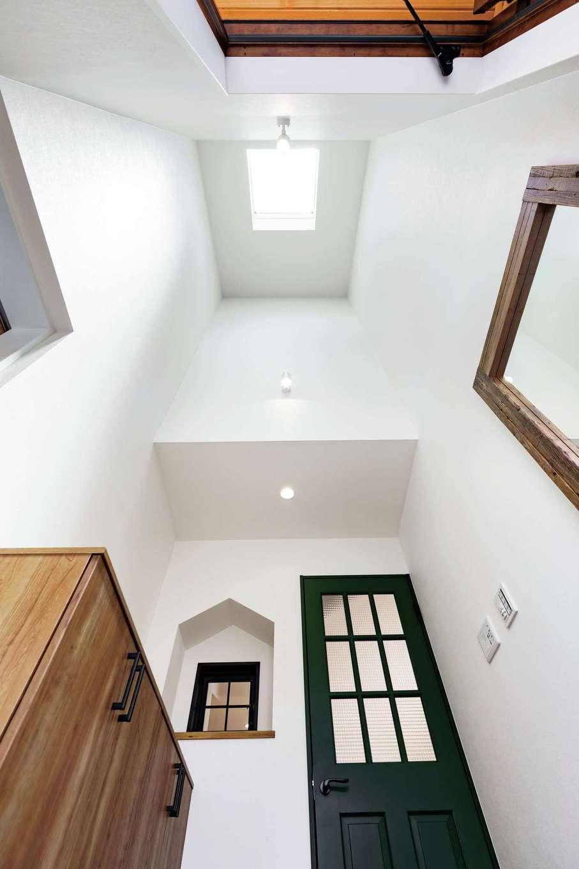 高い吹抜けのある玄関ホール。天窓を設けたことで、暗くなりがちな玄関が常に明るくなる。木枠の全身鏡は空間をより広く見せる効果もある。家の中に家があるみたいなニッチもかわいい