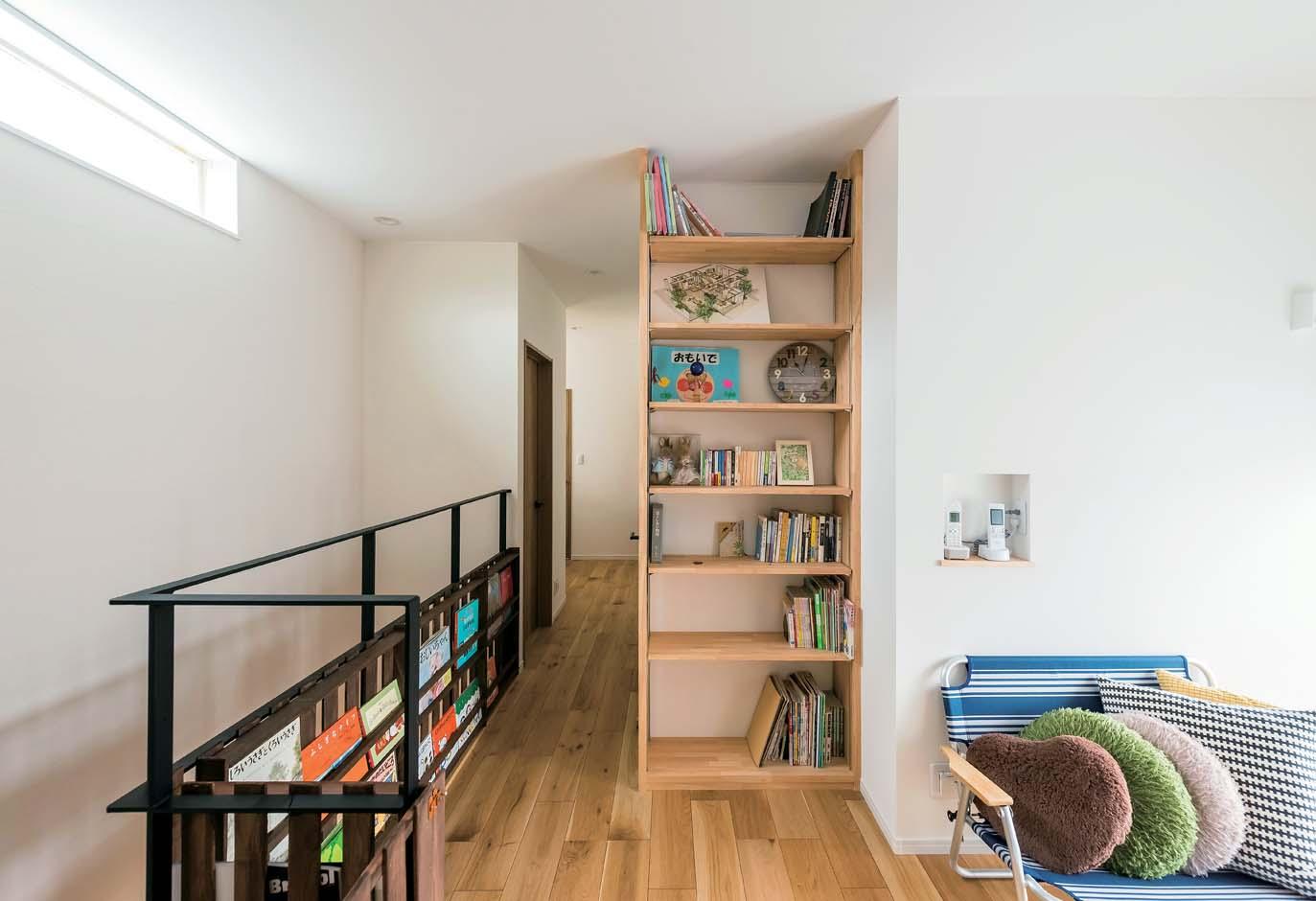 アトリエサクラ【子育て、間取り、ガレージ】2階のホールは、本棚を造作したライブラリーで家族のくつろぎの空間に。アイアンの手すり部分を活用したご主人お手製のマガジンラックもナイスアイデア