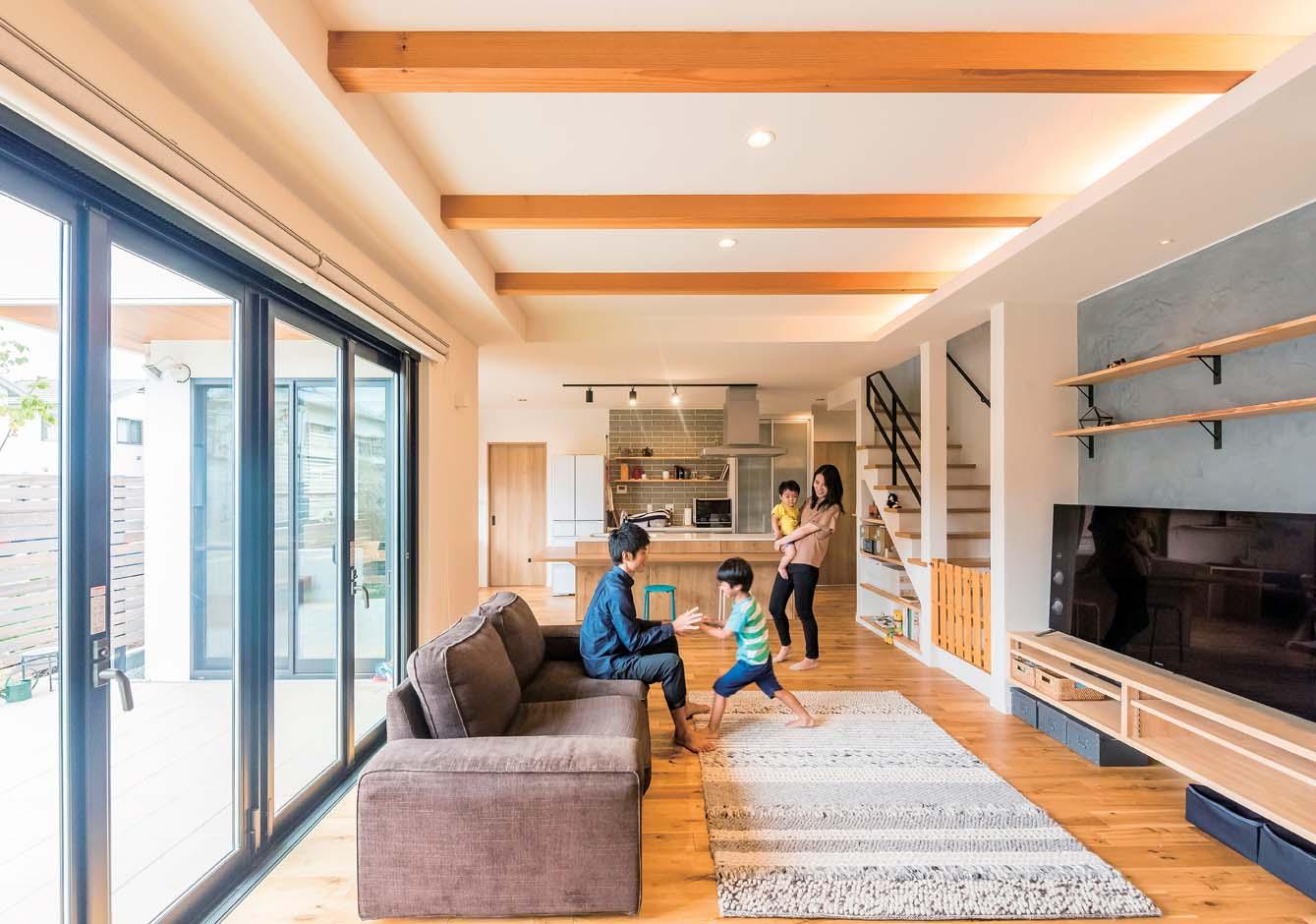 アトリエサクラ【子育て、間取り、ガレージ】LDKは大きめのカウンターがついたアイランドキッチンを主役に。テラスへ続くフルオープンの窓や梁を見せた上げ天井など、細かなこだわりもすべて実現した