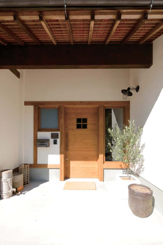 玄関扉は既製品ではなく、施主さんとデザインを練り上げて造作した木の引き戸。昔のままの軒下が化学反応を起こし、新たな魅力が生まれた
